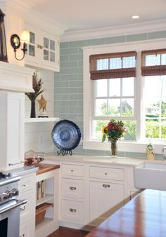 White kitchen with acqua tile to ceiling.  Open shelving mixed with closed