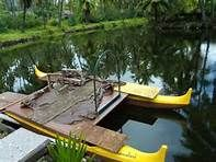 The double hulled Canoe used in the wedding scene in the Elvis Presley movie Blue Hawaii is still in the water at the long shuttered Coco Palms resort, Kauai, Hawaii