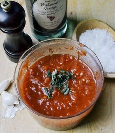 makes about 2 cups, enough for at least 6 pizzas  15-ounce can whole or diced tomatoes  2 cloves garlic, roughly chopped  1 teaspoon balsamic vinegar, or to taste  Olive oil  A few leaves fresh basil, optional  Salt and freshly ground black pepper, to taste