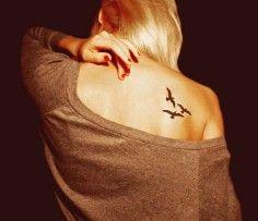 Bird tattoo on upper back for girls