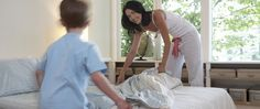 Mother and son keep to their cleaning schedule making a bed.