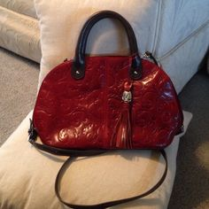 ☀️SUMMER SALE ENDING SUNDAY!!Tignanello red bag This bag has removable crossbody strap, and can be used as a satchel.  It is a deep, darker red embossed leather bag with dark brown leather handles and crossbody stap. Please note the scuff mark on the handle, an a small black mark on the hanging tag. Used for one season. Approx 12 X 7 1/2 X 4 1/2 inches not including the handles. There is one outside zipper pocket! Tignanello Bags Crossbody Bags