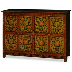 Hand-Painted Tibetan Chest. A bold display of the liveliness inherent to Tibetan art, this cabinet's doors feature an elaborate floral motif captured in exuberant yellow and red tones. Each panel is framed by red trim lined with hand-painted vine patterns. Tibetan furniture.