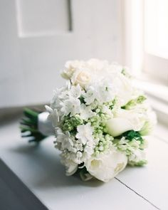 A hand-tied bundle of peonies, narcissus, double freesia, ranunculus, lilac, scilla, and all-white anemones
