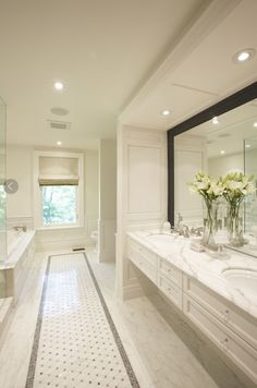 Meredith Heron Design Chic master bathroom design with white bathroom wall mounted vanity with calcutta gold marble counter tops, black beveled mirror, marble basket weave tiles floor and roman shade.. I'd want the toilet separate, probably with a door.
