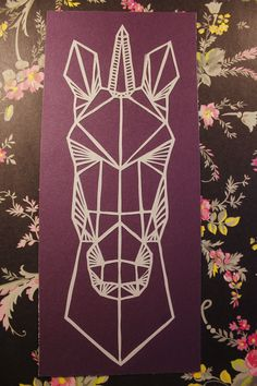 "Hand cut geometric unicorn head from single sheet of white metallic paper, mounted on shimmery purple/maroon quality card.10.5"" X 4.5"""