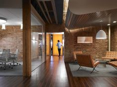 brick walls, glass walls, wood floors. brick extending from reception though conference room. Wood beams.