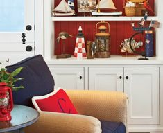 Bold red accent colors for a nautical living room: http://www.completely-coastal.com/2016/04/coastal-house-tours-wayfair-shop-the-look.html Red painted shelf and red home decor accents combined with white, blue and sandy tones.