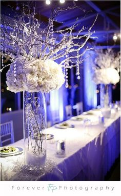 Tall cylinder vases, iced branches with flowers and hanging crystals. This is almost the exact picture in my head
