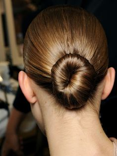 SCULPTED BUN To get this look, as seen at the Givenchy spring 2013 show, part your hair straight down the middle and pull it into a low, tight ponytail. Twist the tail around into a tight bun and pin it neatly in place. Mist on a light-reflective spray, like Bumble and Bumble Shine On (And On...) Finishing Spray, to control flyaways and give hair a glassy sheen.