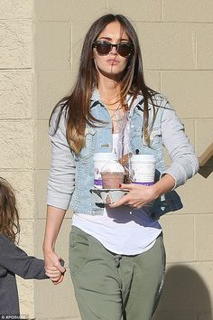 Bonding time:The New Girl star, who held on to little Noah's hand, layered a denim jacket over a casual white vest and shielded from the sun in a pair of chic round sunglasses