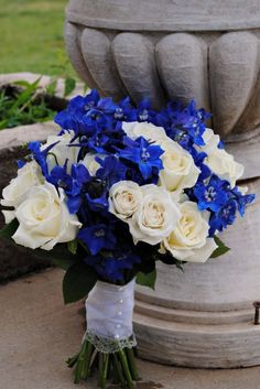 "A ""Bridal bouquet of white 'Escimo' roses, white spray roses, and blue delphinium"""