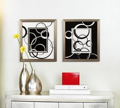Contemporary black and white art makes a graphic impact in hallway decorating.  Here's a home decorating idea - make a style impact by using just simple black and white. This scene shows black and white wall art side by side above a silver tinted side table. The silver and white table accents add to the minimal mood. It's simple, direct and eye-catching.