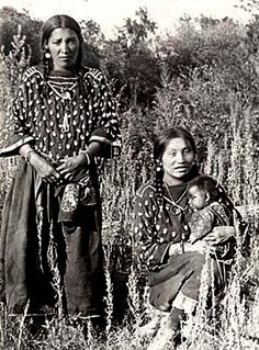 Crow women wearing Elk-Tooth dresses; Victoria Big Shoulder is holding the baby. Photographed: 1890. - National Anthropological Archives, Smithsonian Institution.