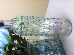 Beaded bottle cover with hummingbird charms.