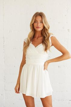 Feeling femme in the Desiree Ruffle Mini Dress! This charming piece features a wrap sweetheart neckline, a tie detail at the waist, and a flouncy hem to complete this flowy silhouette. Available in blue, sage, and white. Top this dreamy look off with the Five and Two Rogue Necklace and you'll be set for your next spring occasion! Sorority Rush, Shawn Mendes, Ruffle Dress, Size Model, Blue Dresses, Sage, Wrap Dress, White Dress, Neckline