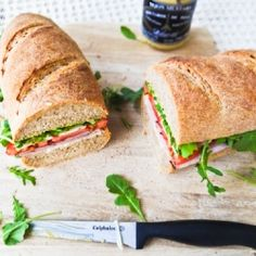 A French inspired sandwich with ham, gruyere, tomato, and arugula on a whole wheat baguette.