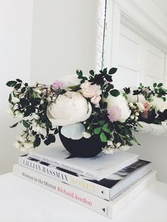 #peony blooms...  http://vicki.fr/1mGqK4B ... Love the juxtaposition of color, books, flowers and the low vase.