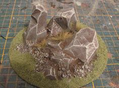 Step 9A - To finish the rock, take some fine modeling flock that ideally should match the color of your gaming mat.