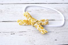 3+inch+bow+in+a+gorgeous+mustard+floral+print,+hand+tied+from+cotton+fabric.+Available+on+a+one+size+fits+all+nylon+band+(shown),+skinny+elastic+in+your+choice+of+size,+or+alligator+clip.+