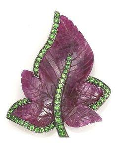 A carved ruby and tsavorite garnet leaf brooch, Sabbadini carved ruby leaf edged with circular-cut tsavorite garnets; signed Sabbadini.