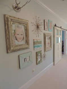 This gallery wall is layered with art and photos from the client's collection. We mixed in some metal and architectural shapes found at HomeGoods. It gives it a collected look and plays off the metal on the barn door.