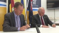 Justice Minister Shane Rattenbury signs the deed of agreement with Community and Public Sector Union national president Alistair Waters.