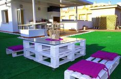 Palet blanco y cojines morados como muebles de jardin, resalta mucho con el verde del cesped