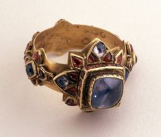 18thC, Islamic. Gold finger-ring. The hoop ornamented with quatrefoil settings, each containing a sapphire and four rubies, connected by pairs of cruciform settings containing rubies. The bezel contains a sapphire and has rubies round the sides; below these, settings which resemble petals with rubies and sapphires. Made of gold.