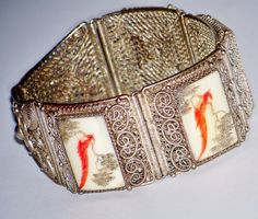 """This is a glorious example of turn of the century Chinese craftsmanship.  The Chinese silver scrimshaw bracelet traces its origins to a date in the early 1930's.    The bracelet features six panels, two silver and four with the ox bone scrimshaws. The four panels of scrimshaw feature a red parrot centered between two bonsai trees, all with similar artwork, each very slightly different in workmanship.    This beautiful vintage bracelet weighs 30 grams and measures 7"""" in length and 1"""" in height with a hidden slip in clasp. The four scrimshaw panels measure 1"""" x 1/2"""" and are securely set in the ornate filigree scrollwork."""