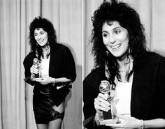 """Cher clutches her Golden Globe for best supporting actress in the movie """"Silkwood"""" at the 1984 Gold Globe Awards. In true 80's fashion, her outfit is business on top and party on the bottom."""