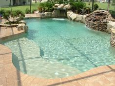 Freeform pool design Orlando pool design Windermere - Custom_lagoon_style_freeform_pool_with_sunshelf_natural_stone_and_pebble_interior
