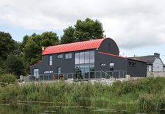 Regular Tours Detached two storey house on the edge of the Shannon demonstrating a considered, detailed design response to the site. Quonset Homes, Quonset Hut, Shed Design, House Design, Steel Barns, Corrugated Roofing, Rural House, Two Storey House, Passive House