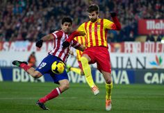 Diego Costa (L) of Atletico de Madrid competes for the ball with Gerard Pique (R) of FC Barcelona during the La Liga match between Club Atletico de Madrid and FC Barcelona at Vicente Calderon Stadium on January 11, 2014 in Madrid, Spain.