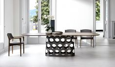 This is a contemporary Jean Table with a Canaletta Walnut table top from Porada.