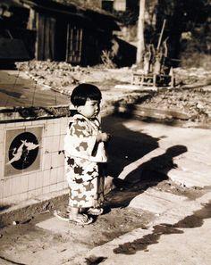 80-G-264846: Japanese Surrender, August-September 1945. Scene at Sasebo, Kyushu, Japan, shows Japanese child. Photographed by crewmember of USS Chenango (CVE 28), released October 19, 1945.