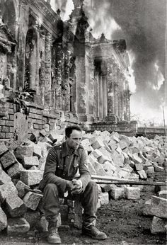 WW II, April 1945 - A battle weary German soldier takes pause in the combat and sits with a look of resignation on his face during the Battle of Berlin as the Reichstag burns behind him. World History, World War Ii, History Online, Berlin 1945, Berlin Germany, Fotografia Social, War Photography, German Army, German Soldiers Ww2