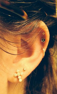 triple cartilage ear piercings with hoop, flower, cross, and studs. love love love!