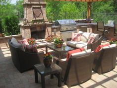 pergola with ceiling fans and lights, a built-in grill and outdoor refrigerator, a granite bar that seats six, a fireplace and an outdoor seating area.