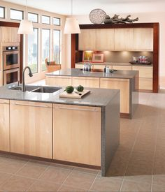 kraftmaid from Lowe's.  Natural Cherry Slab doors help create a bright, modern, open space. Highly functional islands complete the contemporary look.