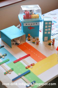 "Cardboard airport with lolly-stick aeroplanes ("",)"