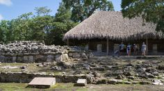 A tour group stops to admire a collection of Mayan ruins
