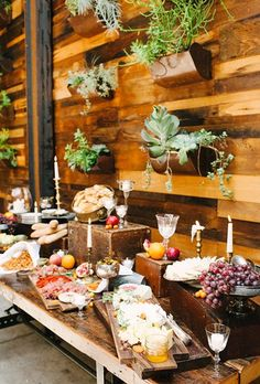 eclectic cheese-and-prosciutto station with assorted fruit displayed against a wall of wild succulents