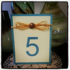 Beach Shell & Raffia Wedding Table Number. Each item is adorned with a natural seashell & adorned with a strand of raffia/straw