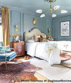 Cozy bedroom with traditional, colorful, boho elements! Animal skin rug, headboard, blue chair, amazing chandelier
