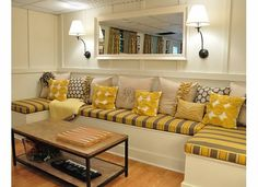 Love this built in DIY banquette for a basement! Bright, practical and cheery use of space!