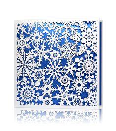 Kartka świąteczna C 802 Biały oraz niebieski perłowy papier, laserowe wycięcie. Kartka świąteczna utworzona z laserowych motywów śnieżynek, umieszczonych na niebieskim tle wkładki. Całość dopełniają ręcznie naklejane kryształki Swarovskiego w kolorze niebieskim.