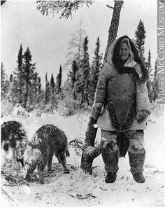 MP-0000.597.198 | Femme portant des vêtements inuits avec deux chiens, à la lisière d'une forêt, 1910-1927