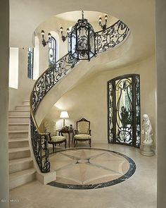 Mediterranean Staircase with Wall sconce, Concrete floors, Custom wrought iron stair railing, Stone Medallions, Arched window Luxury Staircase, Foyer Staircase, Staircase Design, Marble Staircase, Curved Staircase, Railing Design, Wrought Iron Stair Railing, Villa Plan, House Stairs