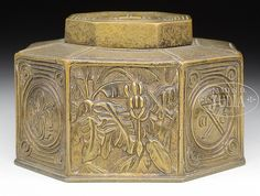 """Tiffany Studios bronze inkwell in the Bookmark pattern has deeply molded panels with various types of vegetation and smaller panels with center medallions. Inkwell is finished in gold and gold dore and is complete with clear glass insert. Marked on the underside """"Tiffany Studios New York 864"""". This exact piece is pictured in Bill Holland's book Tiffany Desk Sets, pg. 155, fig 11-4. SIZE: 4-1/8"""" sq x 2-1/2"""" t. CONDITION: Very good to excellent with darkening of patina. 49032-3"""